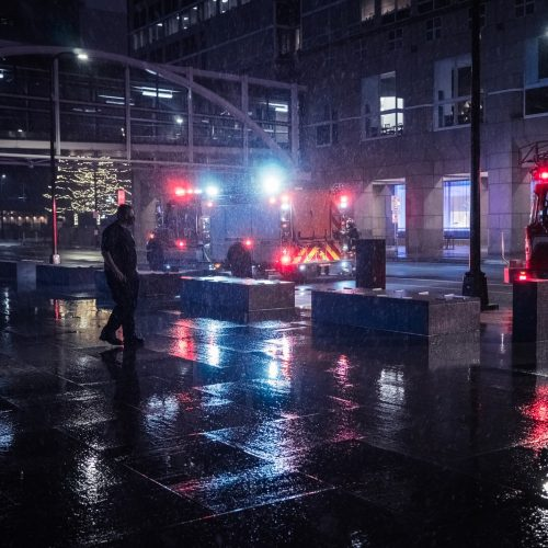 man in black jacket walking on street during night time