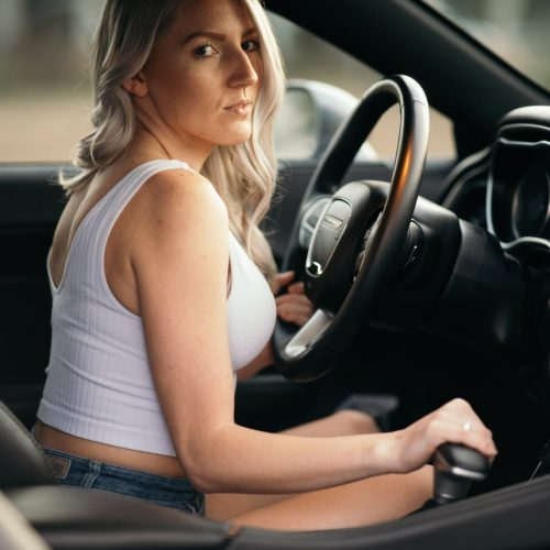 woman in white tank top driving car