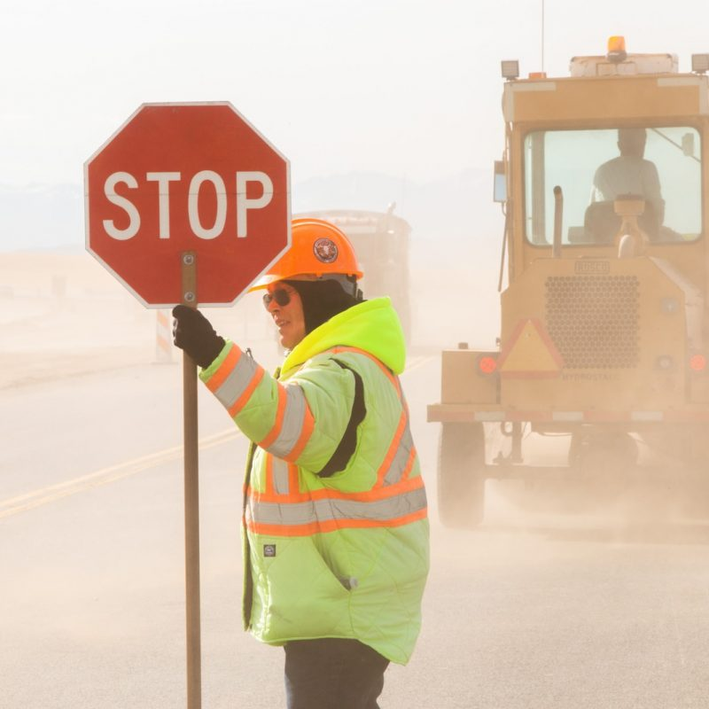 man in green and yellow jacket holding stop sign
