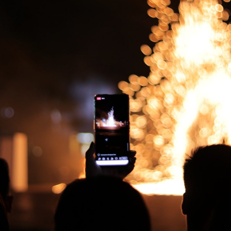 person taking photo of fire during night time